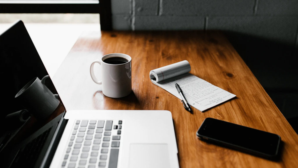 a laptop with coffee and note and cellphone on the side